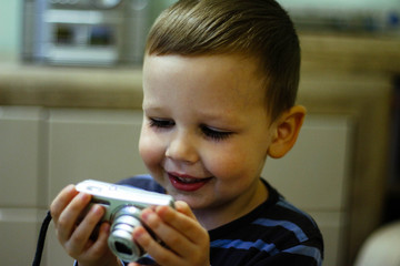 a small boy holds a camera in his hands and smiles, looks at the screen.