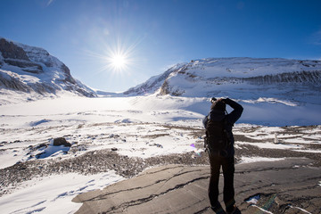 Young male photographer taking picture of Athabasca Glacier