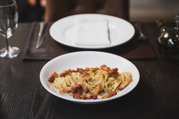 Spaghetti Carbonara made in cheese wheel topping with fried bacon on white plate.