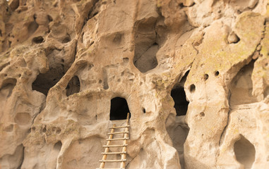 Native American cliff dwelling caves with access ladder at Bandelier National Monument, New Mexico, USA.