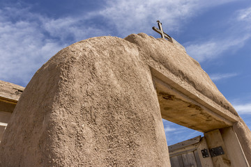 Adobe entryway to an old Spanish catholic church in a Native American Pueblo in springtime, New Mexico, USA.