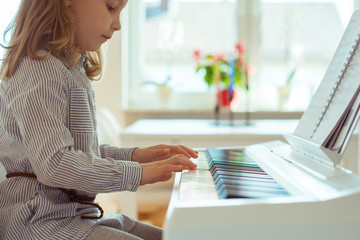 Cute little girl has training with piano