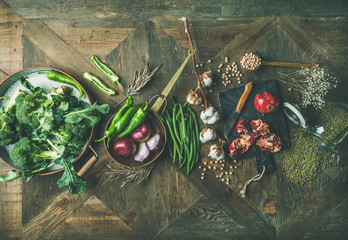 Wall Mural - Winter vegetarian, vegan food cooking ingredients. Flat-lay of seasonal vegetables, fruits, beans, cereals, kitchen utencils, dried flowers, olive oil over wooden background, top view. Healthy food
