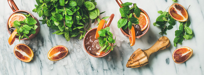 Flat-lay of blood orange Moscow mule alcohol cocktails with fresh mint and ice in copper mugs over white marble background, top view