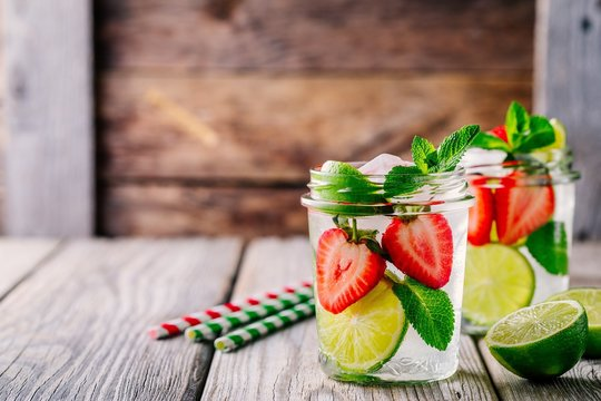 Detox water with  strawberry, lime and mint. Ice cold summer cocktail or lemonade in glass mason jar