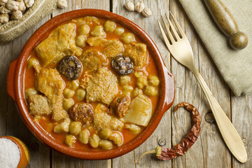 Spanish callos with chickpeas on a wooden table with golden fork