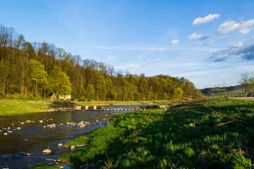 Rzeka Mszanka płynąca w świetle zachodzącego słońca