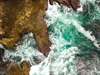 Aerial shot of ocean waves crashing coastline