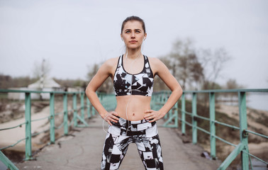 Young athletic woman stand on city bridge, Sporty woman running at morning