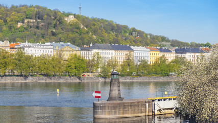 The lighthouse, navigation or orientation landmark built on the riverbank of one of Prague island Zofin. Petrin hill with lookout tower in the background.