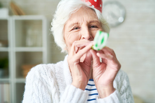 Cheerful hilarious elderly woman with wrinkles having fun alone and blowing party horn while celebrating party at home