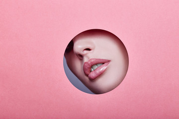 Woman looking in the hole, bright beautiful makeup, big eyes and lips, bright lipstick, professional cosmetics and facial care. Bright colored background and a gap slot in the paper