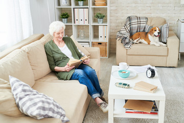 Smiling enjoyable attractive senior woman relaxing with interesting book and sitting on comfortable sofa while Beagle dog lying on armchair