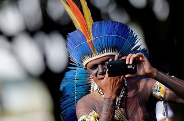 A Brazilian Indigenou checks his face in a mobile phone at the Terra Livre camp, or Free Land camp, during a demonstration in defence of local indigenous people, in Brasilia