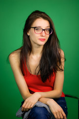 Attractive Smiling Brunette Girl Wearing Optical Eyeglasses Posing in Studio Sitting on the Chair over Green Background.