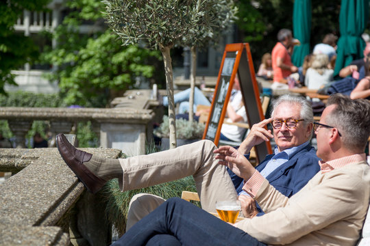 Two older men relaxing at café