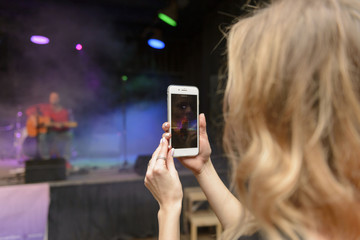 Woman using smartphone to take a video at a concert