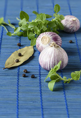 Garlic, green basil, bay leaf with pepper on a mat