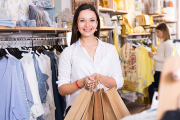 Young woman  carrying  paper bags with purchases in  clothes shop