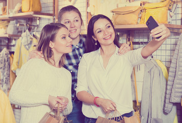 Women  friends making selfie in clothes shop, carrying  paper bags