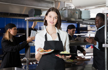 Portrait of female waiter who is standing with order on kitchen