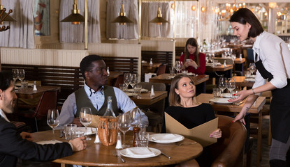 Female waiter is taking order from company who is dining