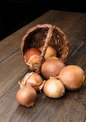 Basket and onion bulbs on a wooden table. Rustic stile