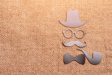 Daddy's day concept, magnets hat, glasses, mustache, Smoking pipe and bow tie on fabric background for bags