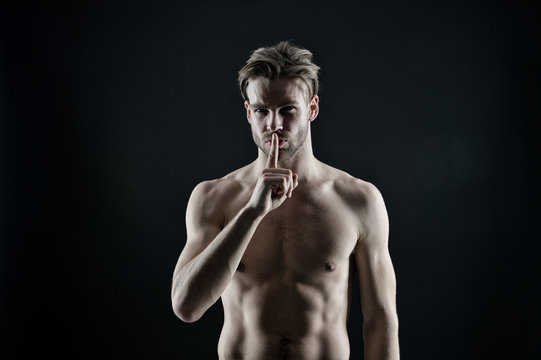 Bodybuilder show silence finger gesture. Sportsman with sexy chest and belly. Bearded man athlete with fit torso. Workout and training activity in gym. Silence and secret concept