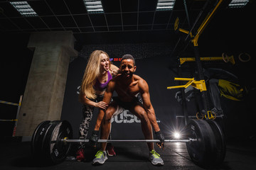 fit woman girl motivates african man while he doing deadlift with heavy barbell. man lifting barbell opposite window. emotional moment of lifting weight. affective lifting in gym. sport couple in gym.