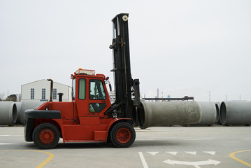 Heavy Forklift loader for warehouse works outdoors with concrete pipes. Industrial production of cement products. Industry manufacturing concept