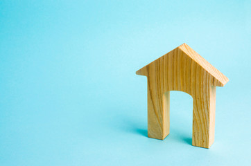 Figurine of a wooden house with a large doorway. Concept of real estate, purchase and sale of housing. Affordable housing at a low price. House for the family.