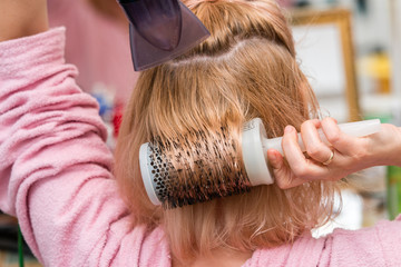 Woman drying her long blond hair with hair dryer and round brush. Close-up.