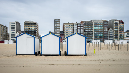 Row of vintage beach huts with buildings in the background