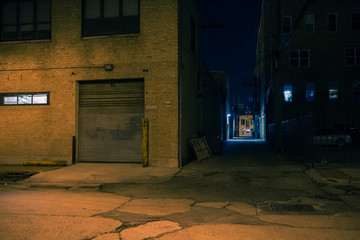 Fotomurales - Dark city street corner and alley with an industrial building entrance at night