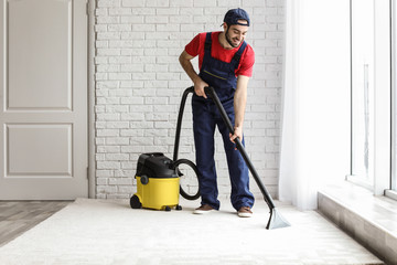 Male worker cleaning carpet with vacuum indoors