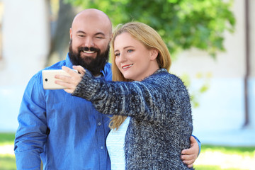 Overweight couple taking selfie in park