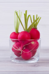 Ripe radishes in clear glass jar. Group of whole radishes in glass on wooden table. Delicious ingredient for spring salad.