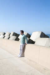 Man yawning on concrete railing at pier