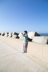 Man taking picture at concrete pier