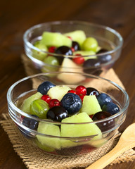 Fresh fruit salad made of cantaloupe melon, blueberry, redcurrant, gooseberry and sweet cherry, photographed with natural light (Selective Focus in the middle of the first salad)