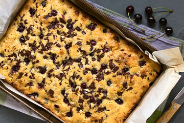 Cherry blondie or blond brownie cake baked with white and dark chocolate, photographed in baking pan overhead with natural light