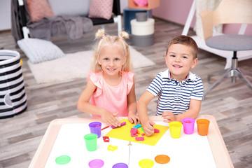 Cute little children modeling from playdough at home