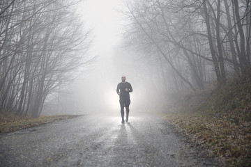 one runner jogging, outdoors mist fog, mysterious forest.
