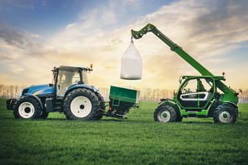 Fototapete - fertilizers are carried in a sacks on the tractor trailer in the field in the spring
