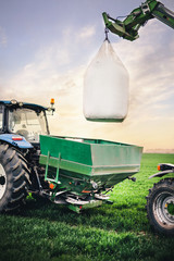 Wall Mural - special machines transport bags with fertilizer to the tractor for further work in the field in the spring