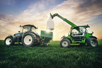 Fototapete - crane puts a sack of fertilizer on a trailer in the field in the spring