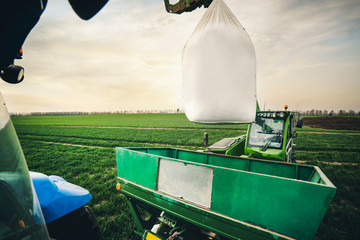 Fototapete - spring works on transportation of fertilizers for the land in the field