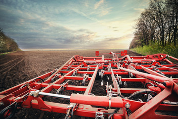 Fototapete - roller with a harrow works on the ground at sunrise in a field in the spring