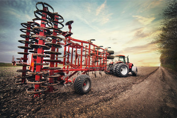 Fototapete - tractor is carries equipment for sowing in the field in the spring